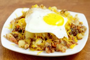 Farmer's Breakfast Skillet Recipe - an easy, hearty breakfast recipe idea with potatoes, ham, bacon, and veggies, topped with cheese and eggs. We love this recipe for brinner too!