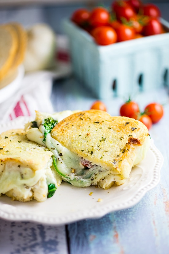 Oven Baked 5 Cheese White Pizza Grilled Cheese Recipe - Baked in the oven to golden, gooey perfection, this deluxe 5 Cheese White Pizza Grilled Cheese is the ultimate cheesy sandwich with 5 types of real cheese, a garlic herb ricotta spread, garlic butter, tangy cherry tomatoes and spinach.