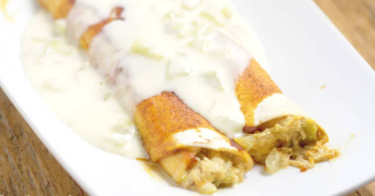 Green Chile Chicken Enchiladas with White Sauce Recipe - these cheesy chicken enchiladas with green chiles and white cheese sauce are a quick and easy dinner recipe idea perfect for the whole family. Our family loves these, and it's a great freezer meal too!
