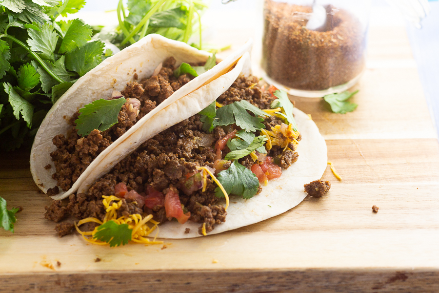 Tacos on a wood cutting board with fresh cilantro and homemade taco seasoning in the background