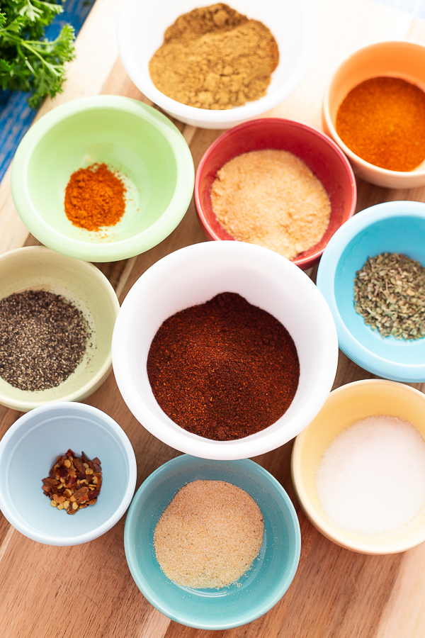 Spices for homemade taco seasoning in small colorful bowls sitting on a wooden cutting board