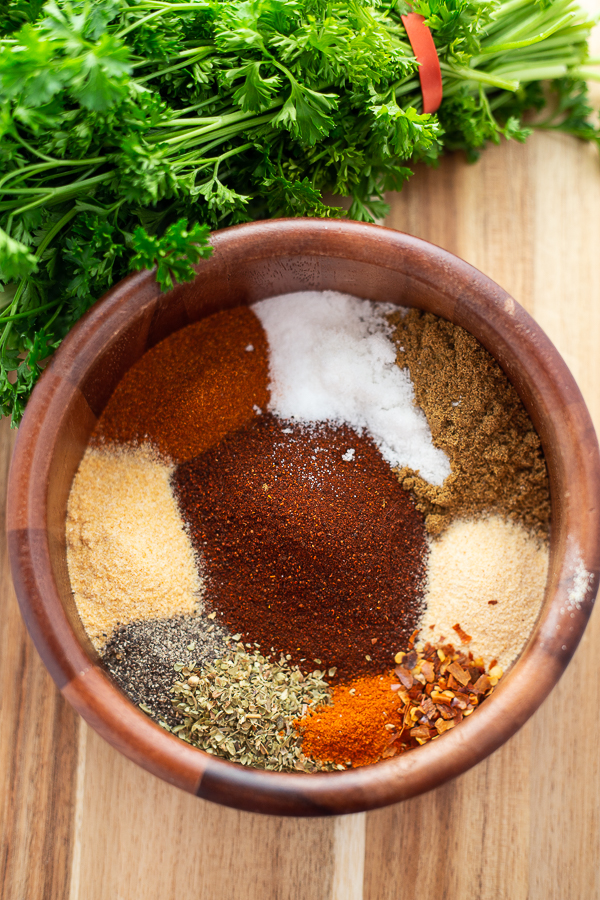 Homemade taco seasoning spices in one wooden bowl, unstirred, sitting on a wooden cutting board with cilantro