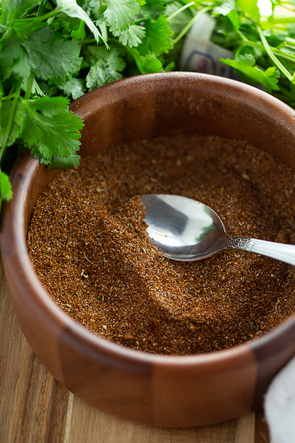 Homemade taco seasoning in a wooden bowl with a spoon it and cilantro in the background