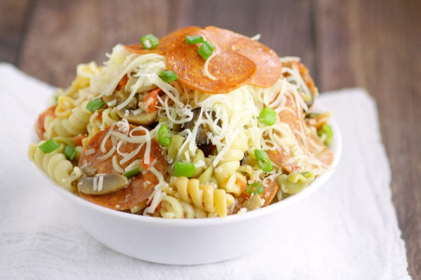 Pizza Pasta Salad Recipe is a delicious, cold pasta salad recipe packed with Italian dressing, veggies and flavor. Great cold pasta salad recipe for a summer side dish, cookout, or BBQ.  Big enough for a crowd too! I won't lie, I could eat the whole bowl of this myself. It is SO GOOD!