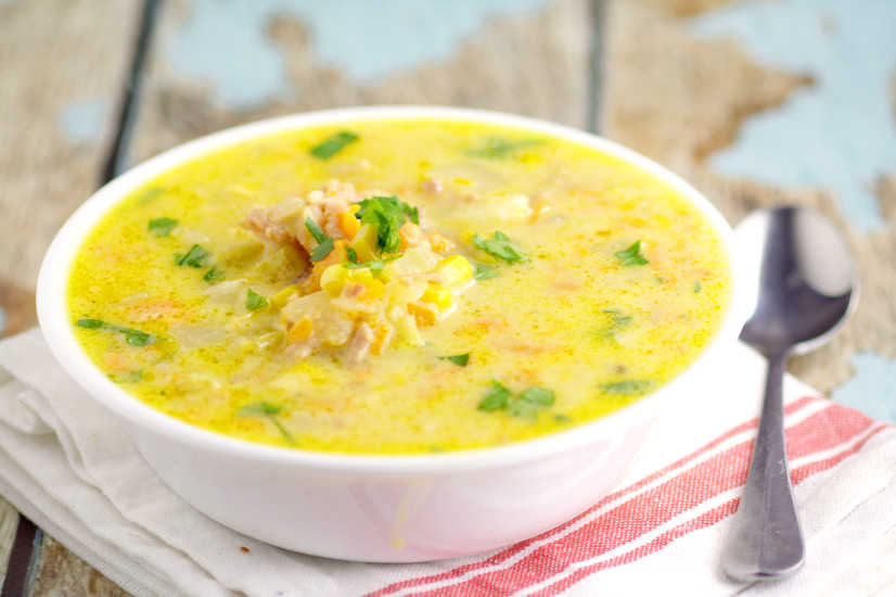 Cheesy ham and corn chowder in a white bowl on a wooden background with a white and red napkin and silver spoon