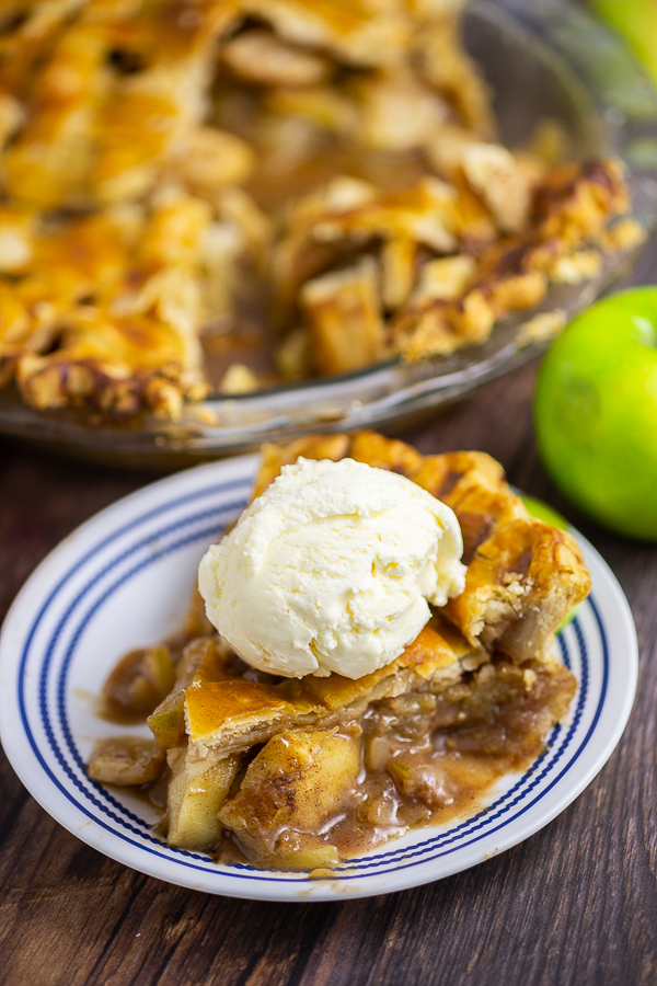 Slice of apple pie on a small plate topped with a scoop of vanilla ice cream. Green apple and pie in a pie dish are behind.