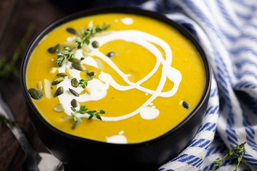 Butternut Squash Bisque in a matte black bowl with a swirl of cream and pepitas and fresh thyme on top sitting on a white and blue linen and a rustic wood background.