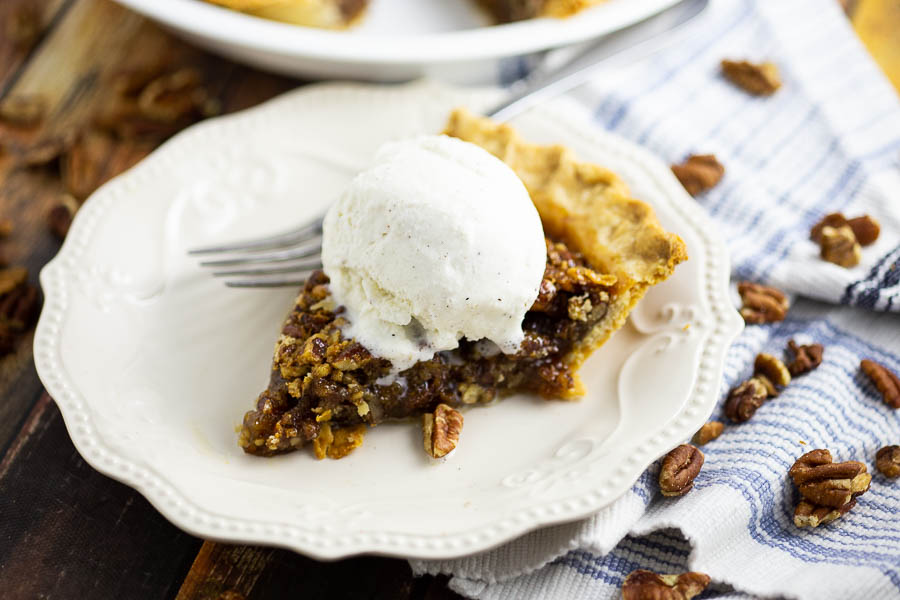 Slice of pecan pie with a scoop of vanilla ice cream on top on a cream colored plate with pecans scattered around on a blue and white striped linen.