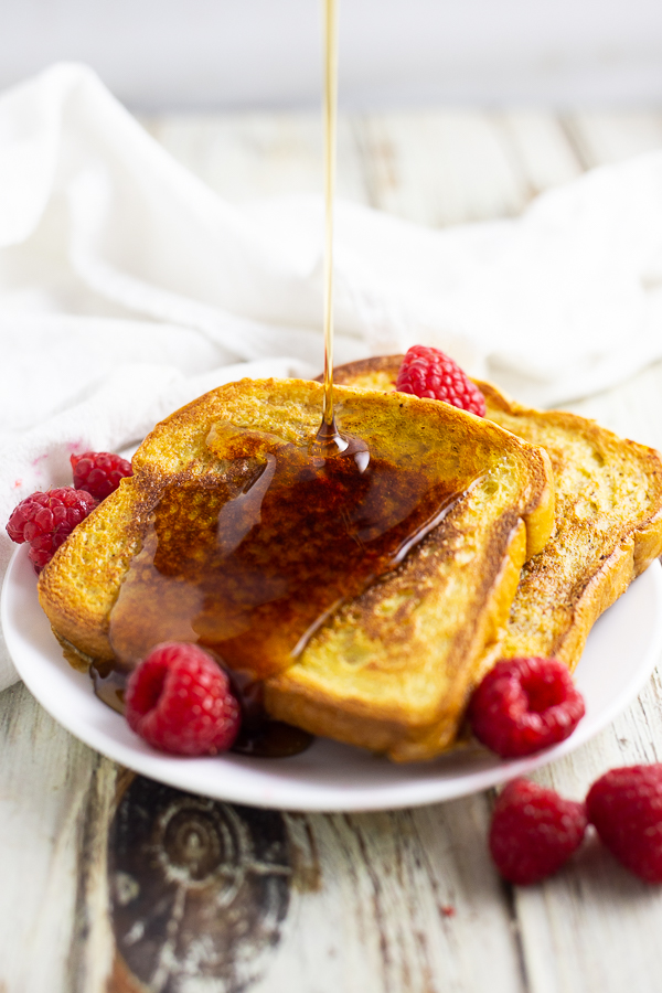 Eggnog French toast on a white plate with fresh raspberries with syrup being drizzled on top.