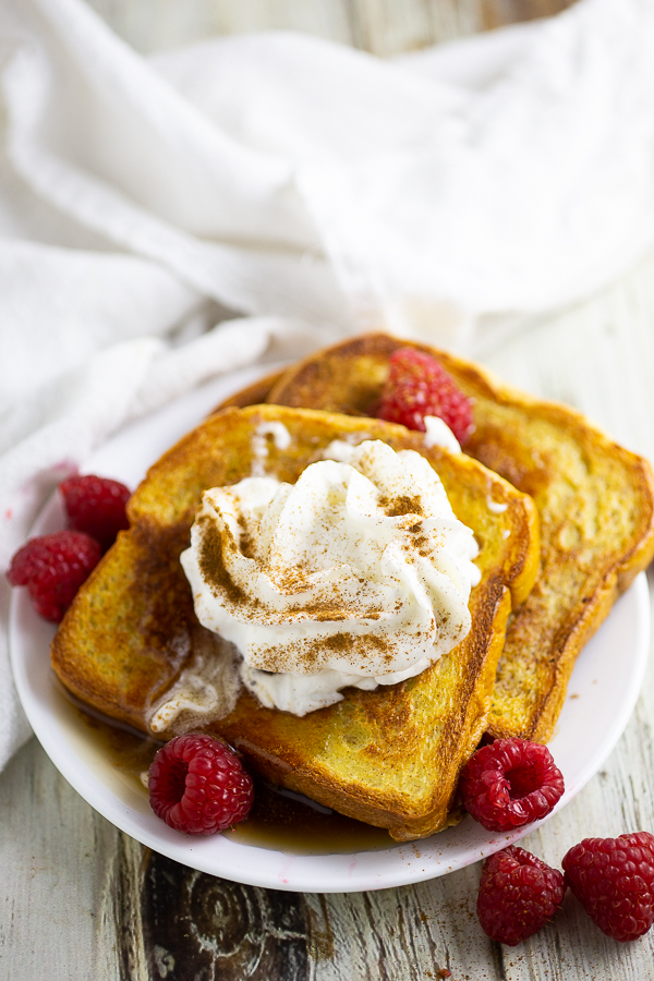 Eggnog French toast with whipped cream and fresh raspberries on a white plate with a white linen in the background