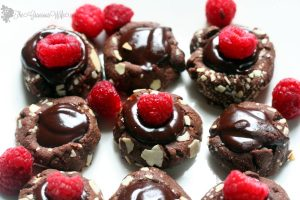 Raspberry Ganache Thumbprints Cookie Recipe - a pretty but easy dessert cookie recipe. Chocolate thumbprints filled with a rich super easy chocolate raspberry ganache and topped with a fresh raspberry. Makes a pretty Christmas cookie too!
