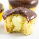 Close up picture of a Boston Cream Pie Cupcakes with a bite taken out on a marble background.