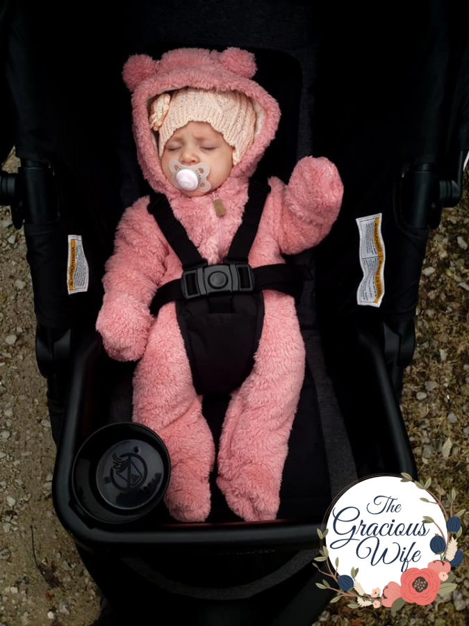 Baby in a stroller in a pink bear bunting sucking a MAM pacifier
