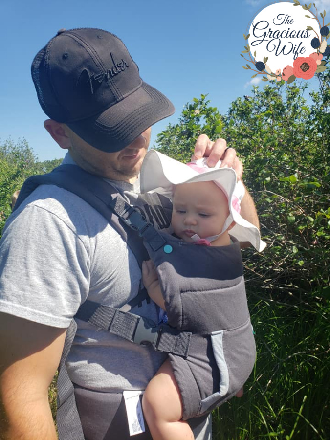 A father carrying a baby in an infantino carrier
