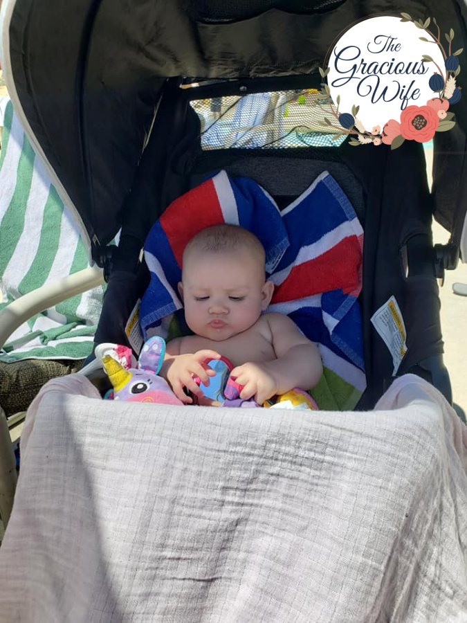 Baby in a stroller covered with a muslin blanket