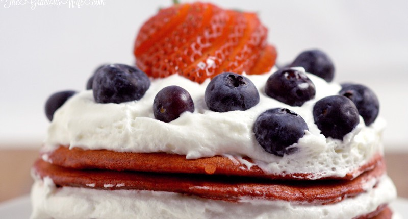 Red Velvet Berry Pancakes Recipe - a delicious breakfast recipe with red velvet pancakes, whipped cream, and fresh berries. The patriotic red white and blue are super cute for a 4th of July breakfast food idea too!