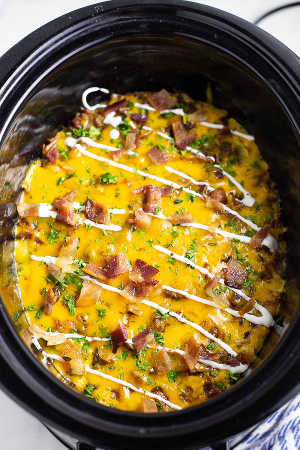 Crockpot breakfast casserole in a slow cooker topped with parsley, sour cream, and bacon