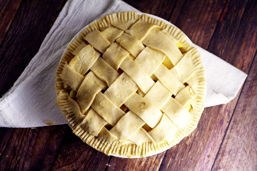 A finished lattice pie crust on a dark rustic wood background with a white linen.
