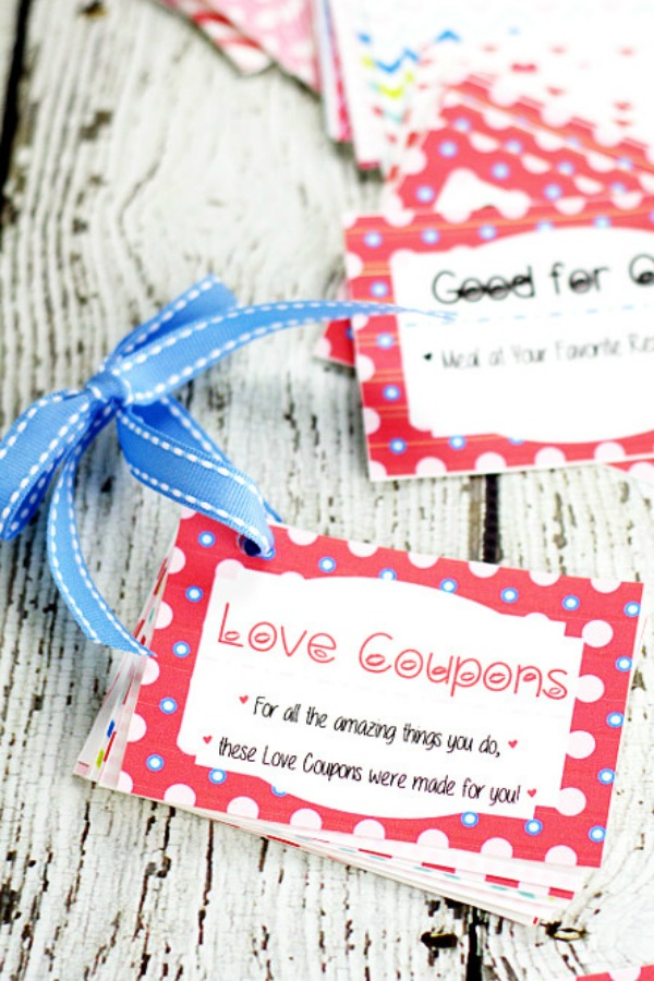 Free Printable Love Coupon book tied together with blue ribbon sitting on a white wood background