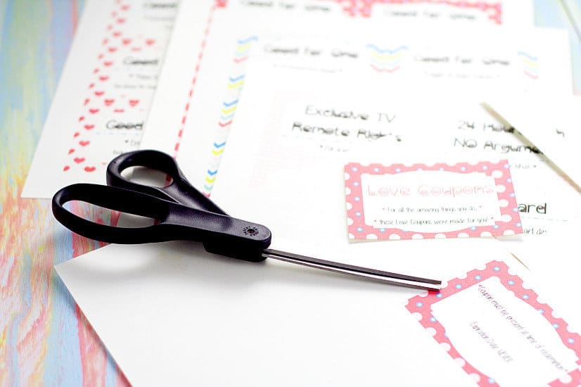 Black scissors on top of printed love coupon book
