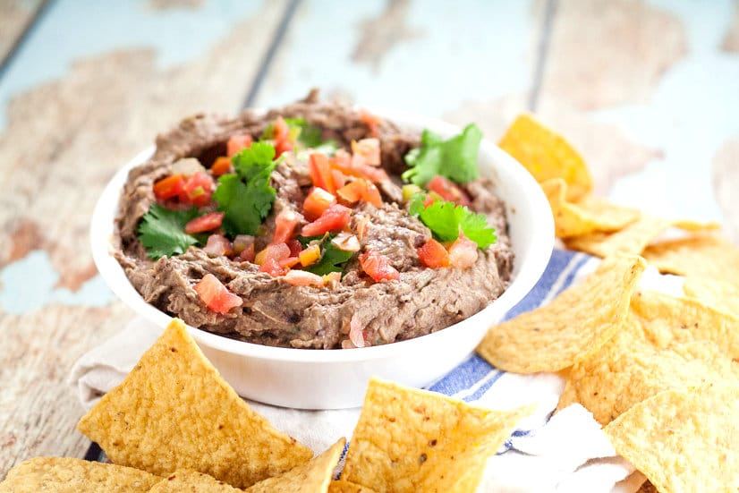 Creamy Black Bean Avocado Dip Recipe - Make this easy and addictive Creamy Black Bean Avocado Dip in just minutes! Makes a healthy snack or heavenly party dip! This is seriously so goodd and ridiculously easy to make.  It goes fast every time we make it and is great game day food and for a crowd.  Can't believe it takes just 8 minutes to make!