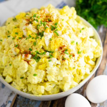 Angle shot of deviled egg potato salad in a wide bowl topped with chives and paprika, next to 2 eggs and herbs on a rustic wooden background