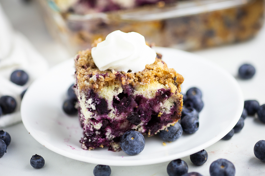 Horizontal image of blueberry buckle topped with whipped cream on a small plate with fresh blueberries scattered around it.