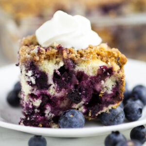side view of blueberry buckle topped with whipped cream on a small plate with fresh blueberries