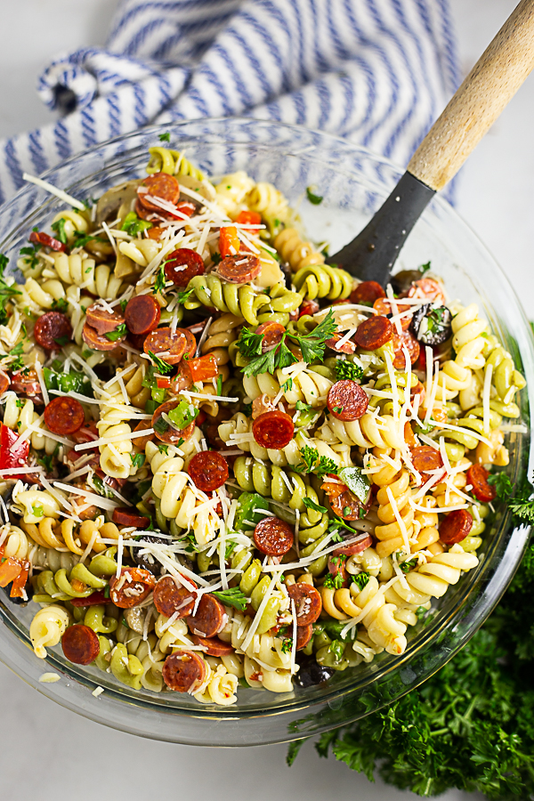 Overhead view of a large bowl of pizza pasta salad with a wooden spoon in it and a striped linen and a bunch of fresh parsley in the background.