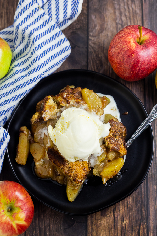 Overhead picture of apple cobbler topped with vanilla ice cream on a plate surrounded by a linen napkin and fresh apples