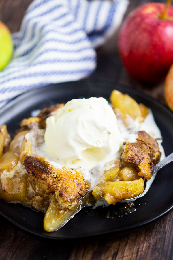 Apple Cobbler on a black plate with a scoop of ice cream on top. Linen napkin and apples are behind the plate