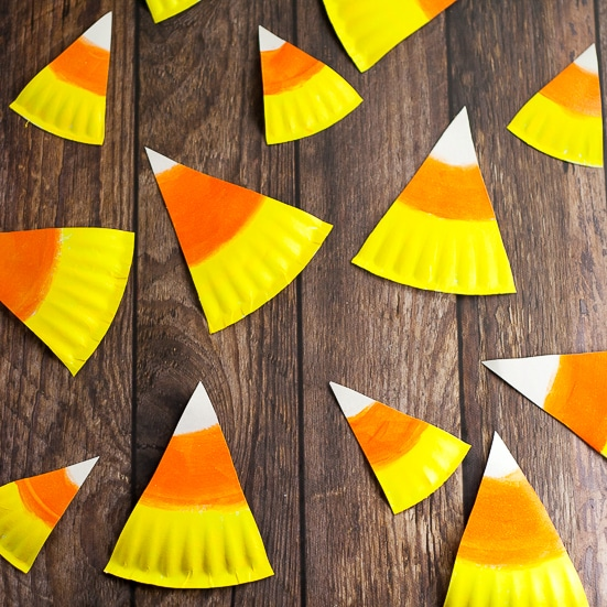 DIY Halloween Paper Plate Candy Corn Banner Tutorial -This cute and festive DIY Paper Plate Candy Corn Banner makes an adorable and cheap DIY Halloween decoration that's perfect for your home or even a Halloween party decoration. So easy to make that even the kids could help!