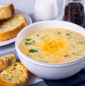 Crockpot broccoli cheese soup in a bowl next to crusty buttered bread