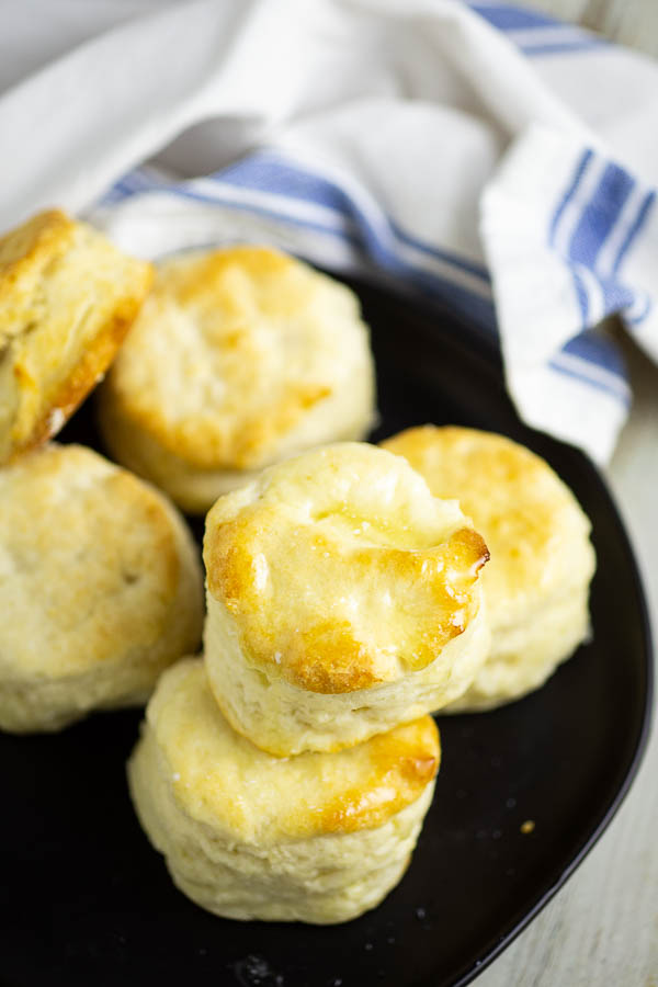 Overhead view of a stack of biscuits on a black matte plate with a white potato sack linen