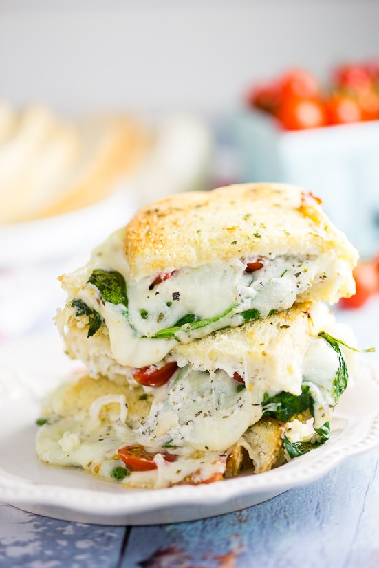 Oven Baked 5 Cheese White Pizza Grilled Cheese Recipe -Baked in the oven to golden, gooey perfection, this deluxe 5 Cheese White Pizza Grilled Cheese is the ultimate cheesy sandwich with 5 types of real cheese, a garlic herb ricotta spread, garlic butter, tangy cherry tomatoes and spinach.