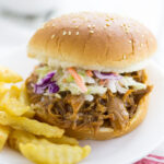 Easy Slow Cooker BBQ Pulled Pork topped with homemade coleslaw on a sesame seed bun next to crinkle cut fries on a small plate