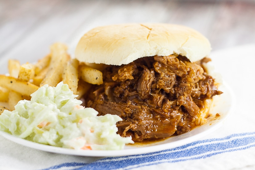 Crock Pot Root Beer Pulled Beef Sandwiches recipe - A 5 ingredient fix-it-and-forget-it slow cooker dinner, this Crock Pot Root Beer Pulled Beef recipe has the perfect combination of tangy sweetness and takes just minutes to throw together! Easy slow cooker recipe perfect for family