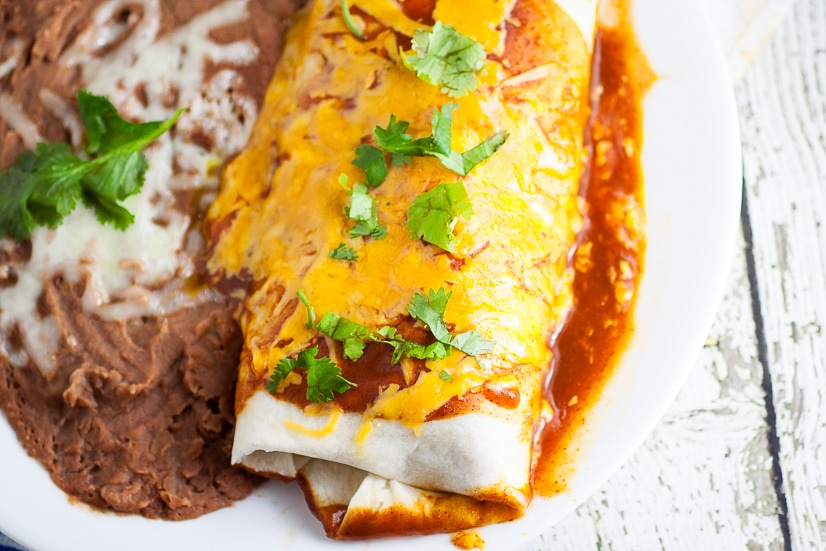Rice and Black Bean Burritos Recipe -Quick and easy Mexican-inspired dinner recipe, these Rice and Black Bean Burritos are filled with flavorful rice and beans and smothered in enchilada sauce and cheese for a yummy vegetarian dinner perfect for Meatless Monday.