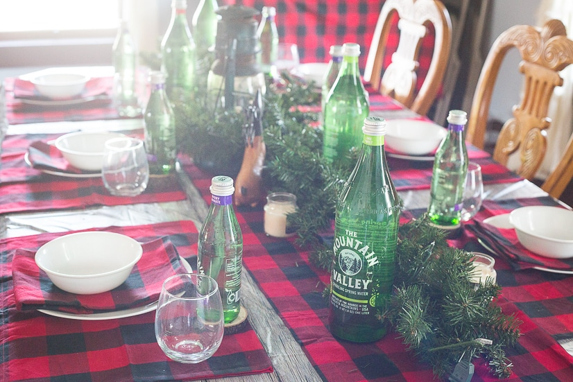 Rustic Christmas and Holiday table decorations and table settings with a lantern centerpiece, evergreen garland, wood slice coasters, red and black buffalo check, and green Mountain Valley Spring Water bottles.
