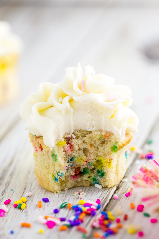Funfetti cupcake with a bite taken out topped with buttercream frosting surrounded by rainbow sprinkles.