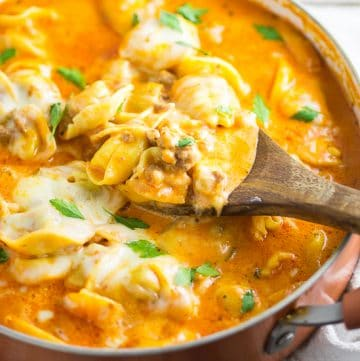 Italian sausage and tortellini nestled in a creamy tomato sauce and topped with gooey mozzarella cheese in this Creamy Sausage and Tortellini make a quick and easy pasta dinner that the whole family will love! A delicious one pan meal that combines the tender, cheese filled pasta with savory sausage and wraps it all in a creamy cheesy tomato sauce. One bite and you'll wonder where it's been all your life!