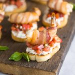 Creamy Bacon Shrimp Bruschetta recipe -Perfect appetizers for entertaining! This Creamy Bacon Shrimp Bruschetta recipe has it all with toasted baguette, a creamy garlic herb and bacon spread, balsamic vinaigrette, and THE BEST fresh basil and tomato bruschetta. Topped with a succulent bacon-wrapped shrimp! Make it for all your summer parties!