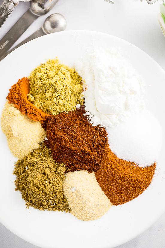 Spices to make homemade fajita seasoning on a white plate