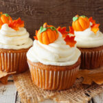 3 frosted cupcakes sitting on burlap, topped with fondant pumpkins and leaves
