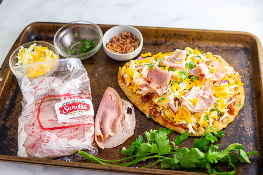 This Flatbread Hawaiian Pizza is quick, easy, and totally delicious! An addicting tangy, salty sweet combination with ham, pineapple, cheese, and a little bacon for good measure.