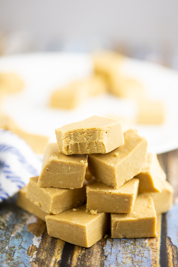 Stack of peanut butter fudge on a blue rustic wood background
