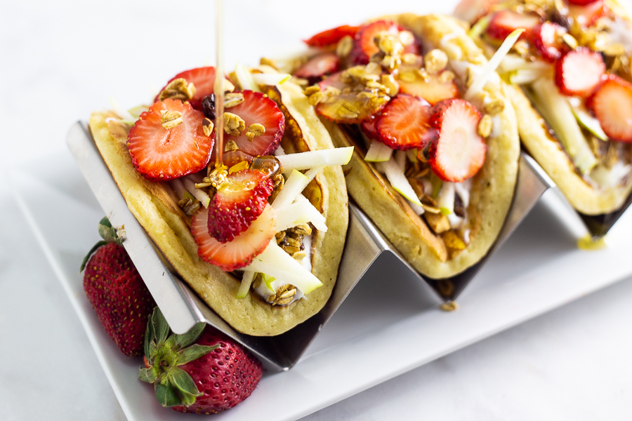 Honey drizzling onto pancake parfait tacos sitting in a taco holder on a white plate
