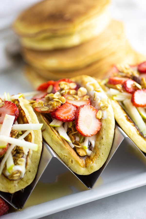 Pancake parfait tacos topped with strawberries in a taco stand on a white plate on a marble counter with pancakes in the background