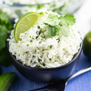 White chipotle lime rice garnished with a fresh lime wedge and sprig of cilantro in a black bowl on a blue wood background