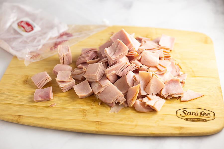 Diced Sara Lee honey ham on a wooden cutting board